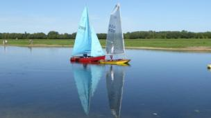 Boats sail past Port Meadow.