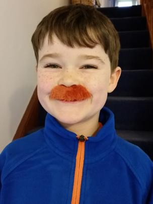Boy wearing a moustache