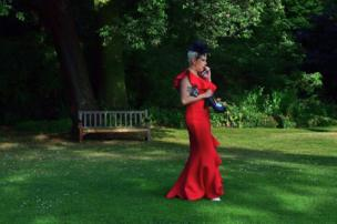 A woman dressed formally for an event takes her heels off to walk on the grass and speak on the phone