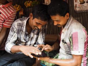 Bangladesh, 2014. Two men look at their phone