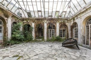 A derelict courtyard containing a grand piano with a glass roof