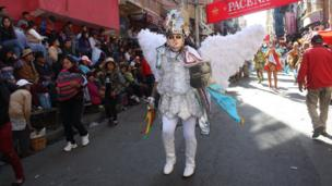 A participant with angel's wings parades through the streets