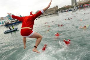 "A participant in a Santa Claus costume jumps into the water during the 108th edition of the ""Copa Nadal"" (Christmas Cup) swimming competition in Barcelona's Port Vell on December 25, 2017"