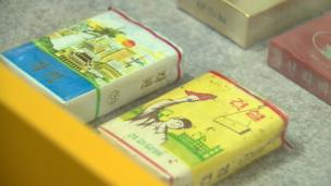 Cigarette cases. 'Paradise(left)' and 'Establishment(right)'. Tobacco smoking is very popular among North Korean men.