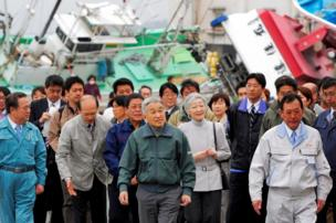 Emperor Akihito (centre) and Empress Michiko (behind Akihito, right), being followed by a number of people, look at overturned ships and the damaged fishing port in Otsu town in Kitaibaraki, about 70km (42 miles) south of the Fukushima Daiichi Nuclear Power Station, 22 April 2011.