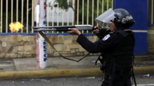 A riot police officer fires a weapon during clashes with students taking part in a protest in Managua on May 28, 2018