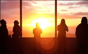 Silhouettes of people watch a sunset