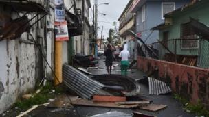 Men survey the damage caused by Hurricane Maria in San Juan, Puerto Rico.