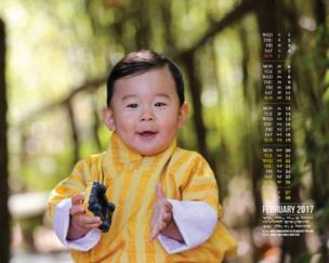 เจ้าชายน้อยในฉลองพระองค์ประจำชาติสีเหลือง และแย้มพระสรวลกับกล้อง ในขณะที่ทรงถือรถของเล่นคันโปรด