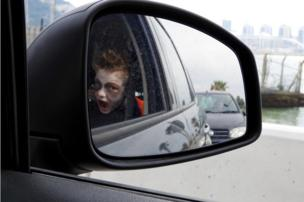 A small boy seen in a wing mirror