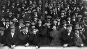 Fans watching West Ham United play Aston Villa, on 4 April 1936, view the eclipse of the sun during play
