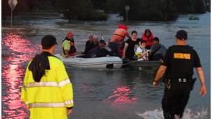 People have had to use boats and inflatable beach toys to escape the water.