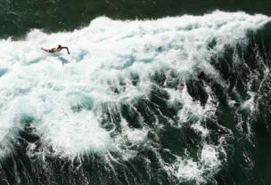 أحد راكبي الأمواج يسقط عن لوح التزلج