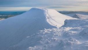 Walkers on a snowy Pen y Fan in the Brecon Beacons