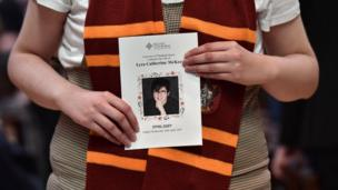 A mourner wearing a Harry Potter scarf holds an order of service.