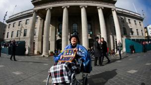 """Sheila O""""Leary, 94, from Clontarf, whose father Thomas Byrne fought in the GPO in 1916, holds a box of his medals on O'Connell Street"""