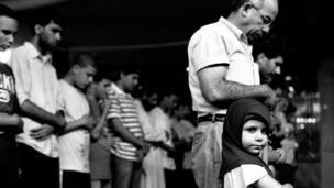 Chica joven en oraciones con su padre, en la Sociedad Musulmana Americana, Brooklyn, 2010.