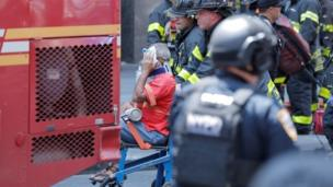 An injured person is taken away in a wheelchair after a car accident in New York