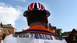 Man wearing a sash and hat covered in union jack, Belfast, 12 July 2017