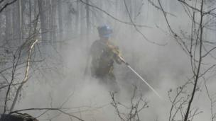 A member of Alberta's Wild Mountain Unit hoses down hotspots in the Parsons Creek area of Fort McMurray, Alberta (07 May 2016)