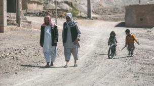 Жители деревни идут по дороге