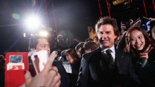 Tom Cruise poses with a fan