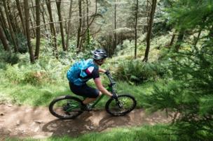 Mujer en bicicleta en un bosque de Gales