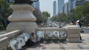 Mujer limpiando el monumento del Ángel de la independencia.