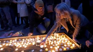 Two women lighting candles