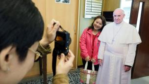 A woman poses for a photograph next to a paper cutout of Pope Francis in the Holy Family Catholic Church in Taipei, Taiwan