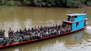 A handout photo provided by the Farc rebels shows them sitting on board a boat in Putumayo province