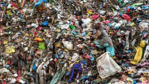 Una mujer casi no puede distinguirse entre la basura de un vertedero. Sus ropas son del mismo color que los residuos.