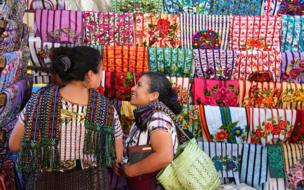 Two women looking at coloured cloth in a market