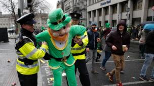 Police officers pretend to arrest a man dressed in a leprechaun outfit in Dublin