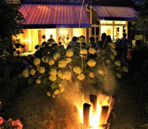 A fire lights a garden with guests socialising in the background