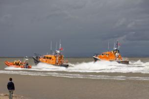 Lifeboats navigate offshore, watched by a young boy