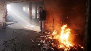 Bir mülteci ateşin yanında ısınıyor.