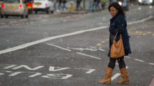 A woman experiences a brief snow shower on Westminster Bridge, in central London.