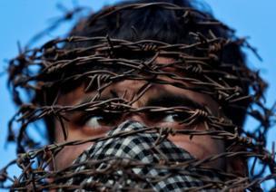 A masked man with his head covered with barbed wire attends a protest in Srinagar in October, following the scrapping of the special constitutional status for Kashmir by the Indian government.