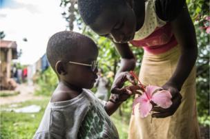 """A prima de Criscent lhe explica o que é uma flor em frente à casa da família em Bundibugyo. """"Adquirir visão é um processo"""", disse Magyezi. """"Com os óculos, Criscent vai aprender a usar seus olhos e o que vê através deles. Assim poderá interpretar o mundo""""."""