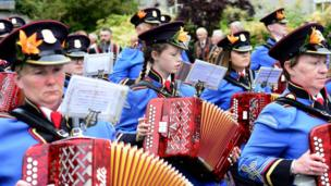 Members of an accordion band play their instruments on parade