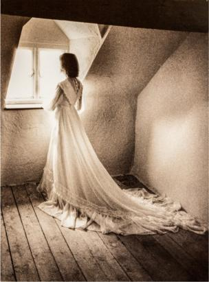 A woman looking out a window in a wedding dress