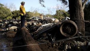 Rescue worker surveys debris after deadly mudslide in California. 10 Jan 2018