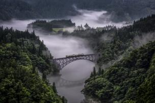 A train crosses a bridge near some mist.