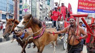 في بنغلادش، ارتدى عامل سلاسل حديدية في تجمع حاشد وطالب بوضع حد أدنى للأجور وتحسين سلامة العمال