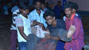 Indian bystanders carry an injured man after an explosion and fire at The Puttingal Devi Temple (Photo: AFP)