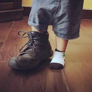 Los pies de un niño que se mide un zapato demasiado grande.