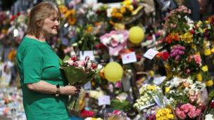 A woman carries flowers to leave with other tributes for the victims of the Grenfell fire