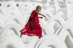 A Novice Monk has a bit of fun at the Hsinbyume Pagoda in Mandalay, Myanmar
