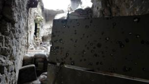 A sheet of metal with bullet holes, looking outside towards ruins